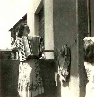 Louisa Yurman playing the accordion on the balcony of her apartment in Rijeka. Circa 1956-7.
